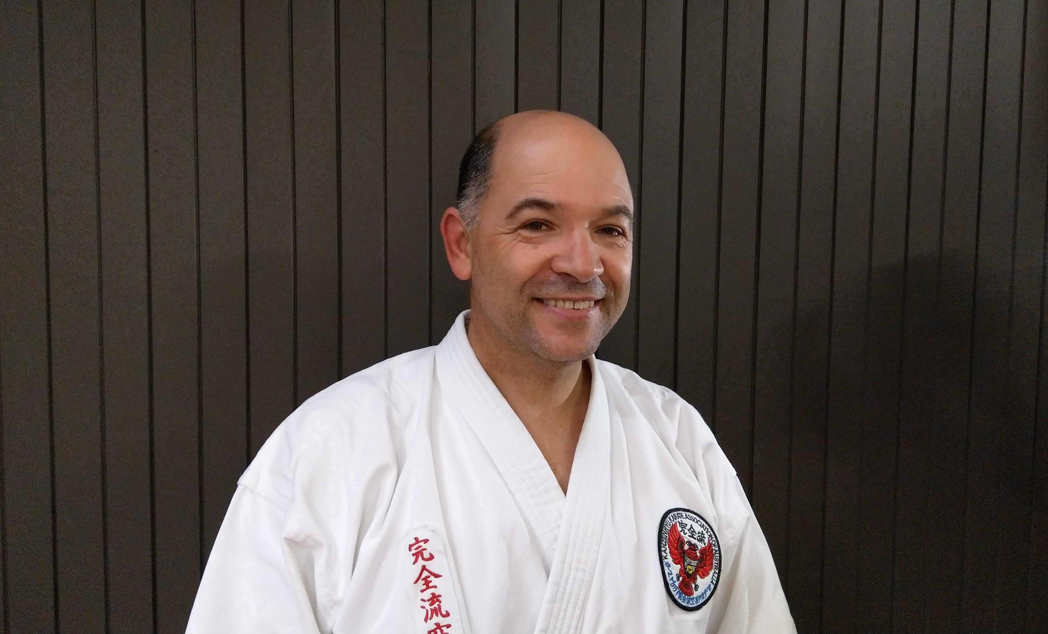 Instructor Senpai Rick De-Oliveira in karate gi smiling at camera