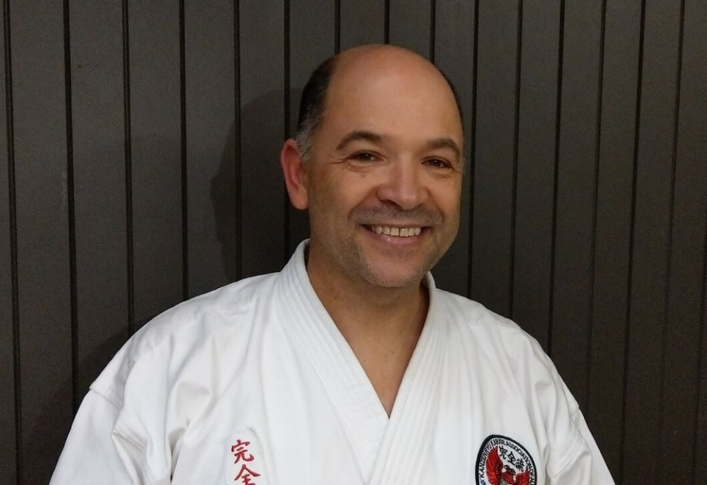 instructor Senpai Rick De-Oliveira smiling at camera in karate gi