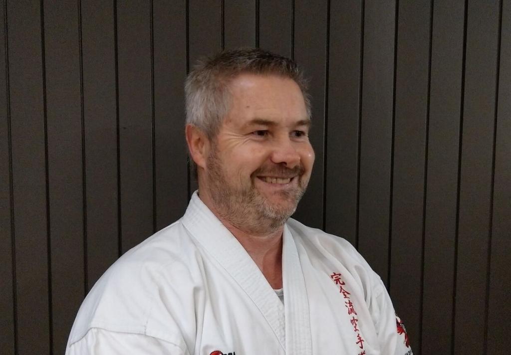 Kyoshi Tyraus Farrelly smiling at camera in karate gi